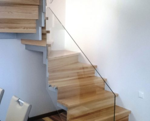 Glass handrails on wooden stairs